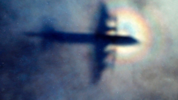 FILE - In this March 31, 2014 file photo, the shadow of a Royal New Zealand Air Force P3 Orion is seen on low level cloud while the aircraft searches for missing Malaysia Airlines Flight MH370 in the southern Indian Ocean, near the coast of Western Australia. In an update released late Monday, April 30, 2018, Ocean Infinity, the American technology company conducting the search, said it had scanned up to 1,300 square kilometers per day since launching its mission in late January. The new scan of ocean floor hasn't found any sign of MH370. (AP Photo/Rob Griffith, File)