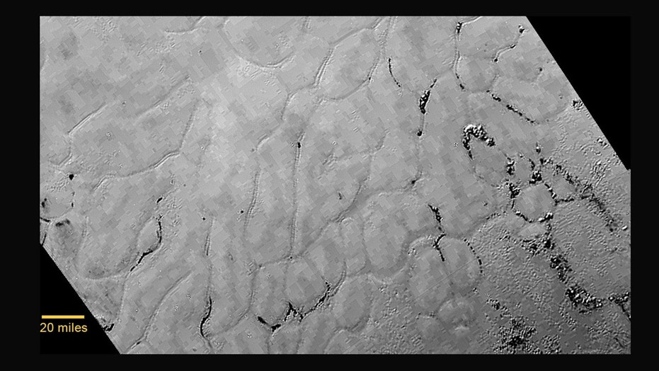This July 14, 2015 photo provided by NASA shows an image taken from NASA's New Horizons spacecraft showing a new close-up image from the heart-shaped feature on the surface of Pluto that reveals a vast, craterless plain. (NASA/JHUAPL/SWRI via AP)