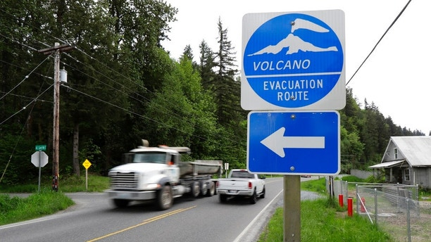 In this May 8, 2018 photo, a volcano evacuation route sign directs traffic and pedestrians to an area of higher ground near Orting, Wash. should nearby Mount Rainier erupt or trigger a lahar mud flow. The eruption of the Kilauea volcano in Hawaii has geologic experts along the West Coast warily eyeing the volcanic peaks in Washington, Oregon and California, including Rainier, that are part of the Pacific Ocean's ring of fire. (AP Photo/Ted S. Warren)