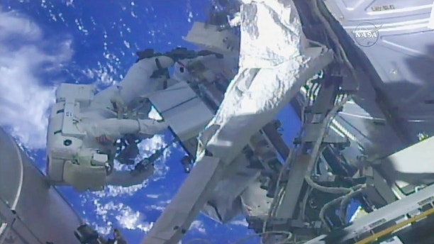 In this frame from NASA TV, NASA astronaut Ricky Arnold, left, and NASA astronaut Drew Feustel work on shuffling around a couple of space station pumps at the International Space Station on Wednesday, May 16, 2018. (NASA TV via AP)