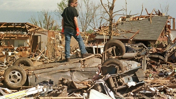 A man stands atop a smashed car May 5 in a tornado-ravaged neighborhood south of Oklahoma City. Officials allowed residents back into the neighborhoods to begin retrieving personal items from their homes destroyed by the F5 tornado that smashed the area May 3. At least 44 people were killed and hundreds injured when tornadoes smashed through parts of Oklahoma and Kansas.  JM/JP/ME - RP1DRIHIHSAA