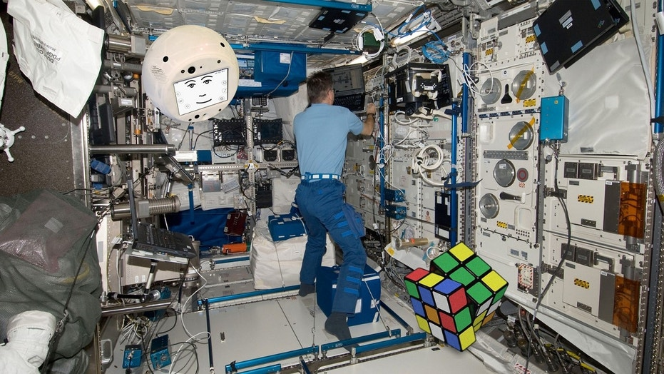 CIMON is pictured here, flying around in zero gravity with a human colleague and a Rubik's cube.