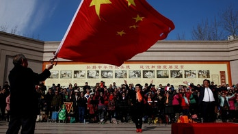 A man waves the Chinese national flag as an amateur choir performs in a park in a residential neighbourhood in Beijing, China February 28, 2017.  REUTERS/Thomas Peter - RTS10PYV