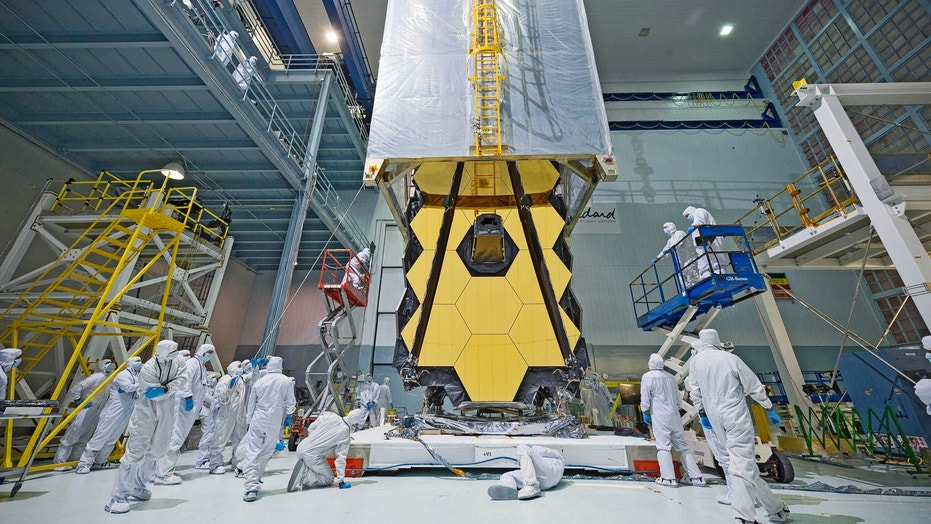 Engineers lower a clean tent over the James Webb Space Telescope during its assembly. NASA announced June 27 that the flagship space telscope's launch will be delayed to March 2021 due to ongoing technical problems.