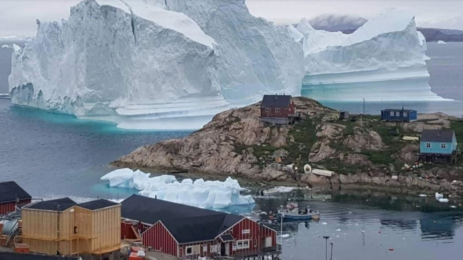 A massive iceberg is looming near a tiny village in Greenland.
