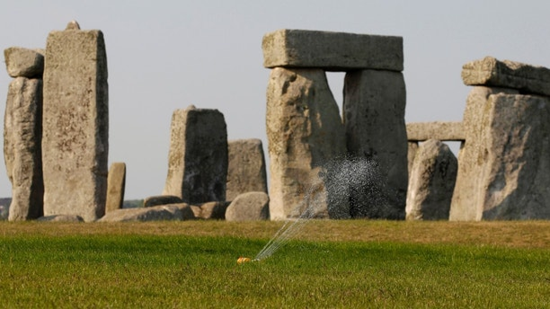 File photo - A sprinkler waters the grass surrounding the ancient site of Stonehenge, southern England April 30, 2011.