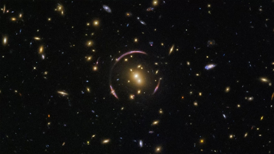 Hubble captured this image of the universe's many galaxies, with an Einstein ring to boot. When the light from distant galaxies warps around an extremely large mass, like a galaxy cluster, it creates this elegant ring. Credit: ESA/Hubble & NASA; Acknowledgment: Judy Schmidt
