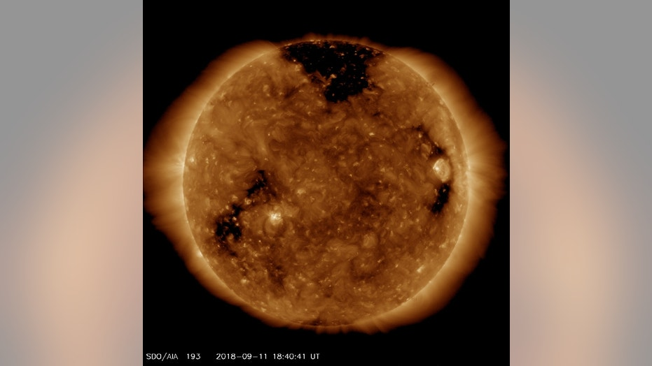 NASA's Solar Dynamics Observatory spacecraft captured this image of a giant hole (dark patch at top) in the sun's outer atmosphere, or corona, on Sept. 11, 2018.