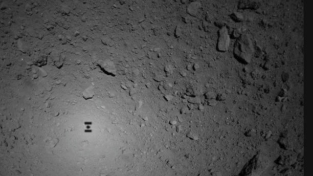 This image provided by the Japan Aerospace Exploration Agency (JAXA), shows the shadow, center left, of Japanese unmanned spacecraft Hayabusa2 over the asteroid Ryugu Friday, Sept. 21, 2018. The Japanese spacecraft Hayabusa2 released two small Minerva-II-1 rovers on the asteroid on Friday in a research effort that may provide clues to the origin of the solar system. JAXA said confirmation of the rovers' touchdown has to wait until it receives data from them on Saturday. (JAXA via AP)