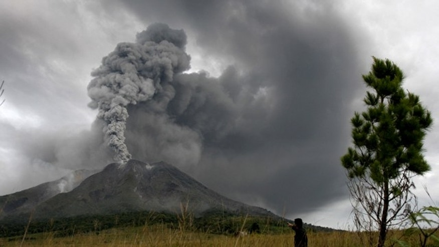Mount Sinabung spews volcanic materials into the sky in Karo, North Sumatra, Indonesia, Monday, Aug. 30, 2010. The volcano that had been dormant for more than four centuries erupted for the second day in a row Monday, spewing out towering clouds of ash and forcing the evacuation of more than 21,000 people. (AP Photo/Roone Patikawa)