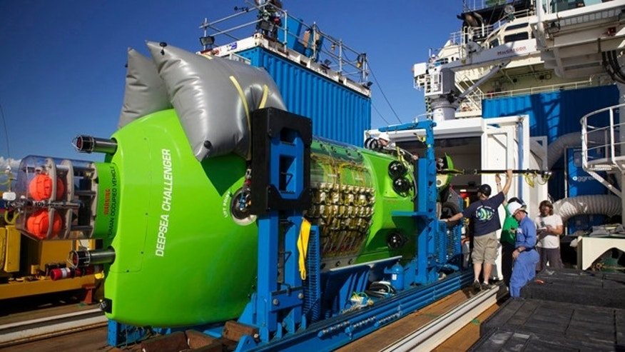 Crews examine the DEEPSEA CHALLENGER submersible aboard the Mermaid Sapphire off the coast of Australia. The sub is the centerpiece of DEEPSEA CHALLENGE, a joint scientific project by explorer and filmmaker James Cameron, the National Geographic Society and Rolex to conduct deep-ocean research.