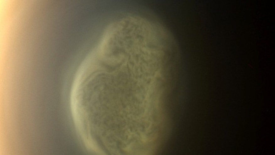 June 27, 2012: This true color image captured by NASA'S Cassini spacecraft before a distant flyby of Saturn's moon Titan shows a south polar vortex, or a swirling mass of gas around the pole in the atmosphere of the moon.