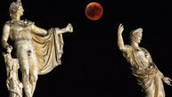 """TOPSHOT - A picture shows the full moon during a """"blood moon"""" eclipse beside a statue of ancient Greek goddes Hera (R) and god Apollo in central Athens on July 27, 2018. - The longest """"blood moon"""" eclipse this century began on July 27, coinciding with Mars' closest approach in 15 years to treat skygazers across the globe to a thrilling celestial spectacle. (Photo by Aris MESSINIS / AFP)        (Photo credit should read ARIS MESSINIS/AFP/Getty Images)"""