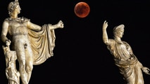 "TOPSHOT - A picture shows the full moon during a ""blood moon"" eclipse beside a statue of ancient Greek goddes Hera (R) and god Apollo in central Athens on July 27, 2018. - The longest ""blood moon"" eclipse this century began on July 27, coinciding with Mars' closest approach in 15 years to treat skygazers across the globe to a thrilling celestial spectacle. (Photo by Aris MESSINIS / AFP)        (Photo credit should read ARIS MESSINIS/AFP/Getty Images)"
