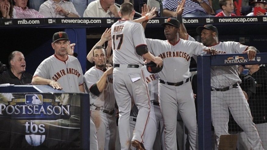Oct. 11: San Francisco Giants' Aubrey Huff (17) is congratulated by teammates after scoring during the seventh inning on a fielders choice in Game 4 of baseball's National League Division Series against the Atlanta Braves.