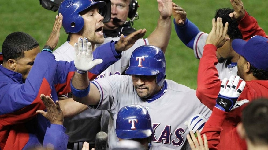 Texas Rangers' Bengie Molina, center, is greeted at the dugout after a three-run home run in the sixth inning of Game 4 of baseball's American League Championship Series against the New York Yankees Tuesday, Oct. 19, 2010, in New York. (AP Photo/Paul Sancya)