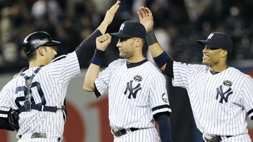 Oct. 20: New York Yankees' Jorge Posada (20), Derek Jeter, center, and Robinson Cano celebrate after beating the Texas Rangers 7-2 in Game 5 of baseball's American League Championship Series.