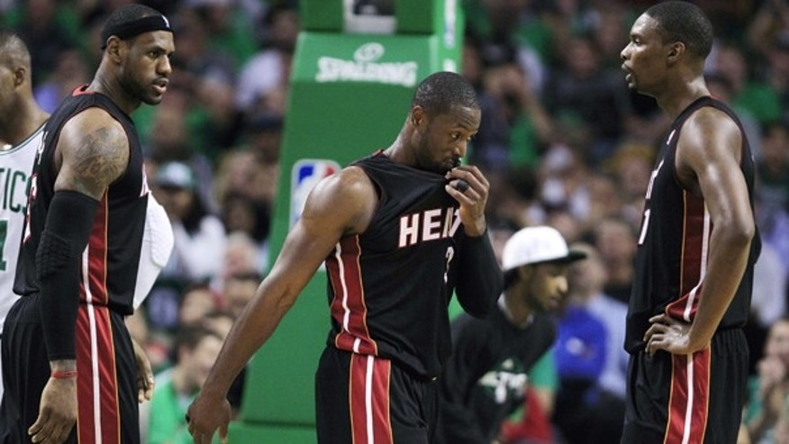 Oct. 26: Miami Heat forward LeBron James, left, talks with teammates Dwyane Wade, center, and Chris Bosh, right, while trailing the Boston Celtics during the first half of an NBA basketball game in Boston.