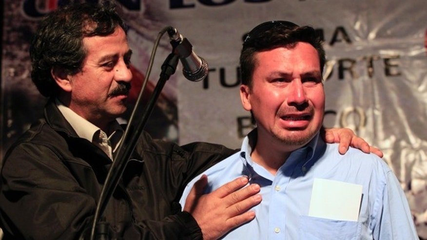 Oct. 19: Rescued miner Edison Pena, right, cries while fellow rescued miner Juan Illanes supports him during a ceremony honoring the miners in Caldera, Chile.