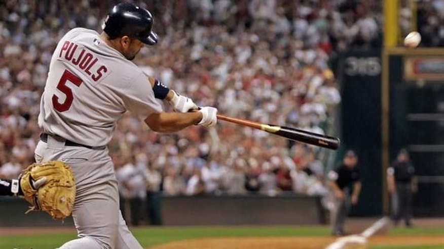 St. Louis Cardinals' Albert Pujols hits a three run homer in the ninth inning in Game 5 of their National League Championship Series in Houston, Monday, Oct. 17, 2005. Cardinals' David Eckstein and Jim Edmonds scored on the home run.  (AP Photo/David J. Phillip)