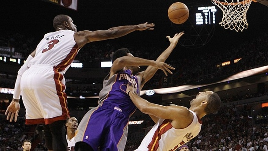 Nov. 17: Phoenix Suns guard Josh Childress, center, shoots as he is foulde by Miami Heat forward Juwan Howard (5) as guard Dwyane Wade (3) defends in the second quarter during an NBA basketball game in Miami.