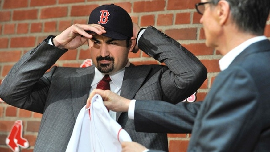 Dec. 6: Boston Red Sox first baseman Adrian Gonzalez puts on his new team's cap as team owner John Henry, right, holds out his new jersey during a news conference at Fenway Park.