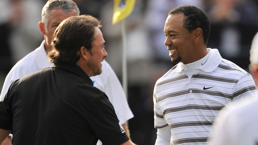 Graeme McDowell, of Northern Ireland, left, and Tiger Woods shake hands after completing the third round of the Chevron World Challenge golf tournament at Sherwood Country Club in Thousand Oaks, Calif., Saturday, Dec. 4, 2010. (AP Photo/Gus Ruelas)