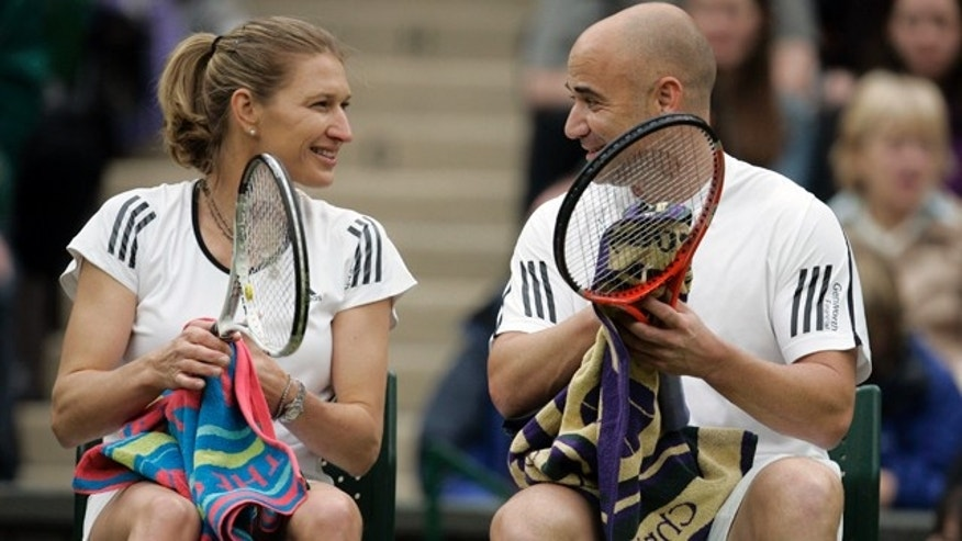 FILE - This May 17, 2009, file photo shows former tennis champion Andre Agassi with his wife, former tennis champion, German-born Steffi Graf, during a break in a mixed double tennis match against British tennis player Tim Henman and former tennis champion Kim Clijsters during a test event on Wimbledon's Centre Court in London.