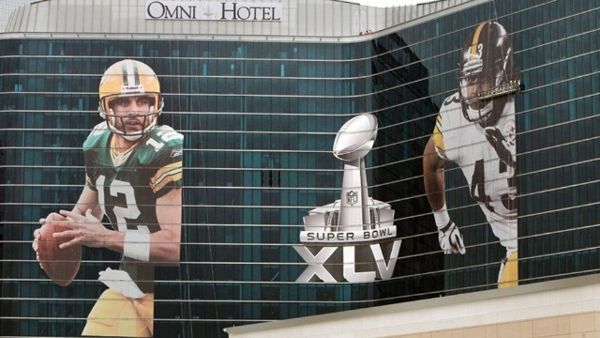 Jan. 31: Giant images of Pittsburgh Steelers' Troy Polamalu, right, and Green Bay Packers' Aaron Rodgers flank a Super Bowl XLV icon, during installation on the exterior of the new Omni Dallas Convention Center Hotel in Dallas.