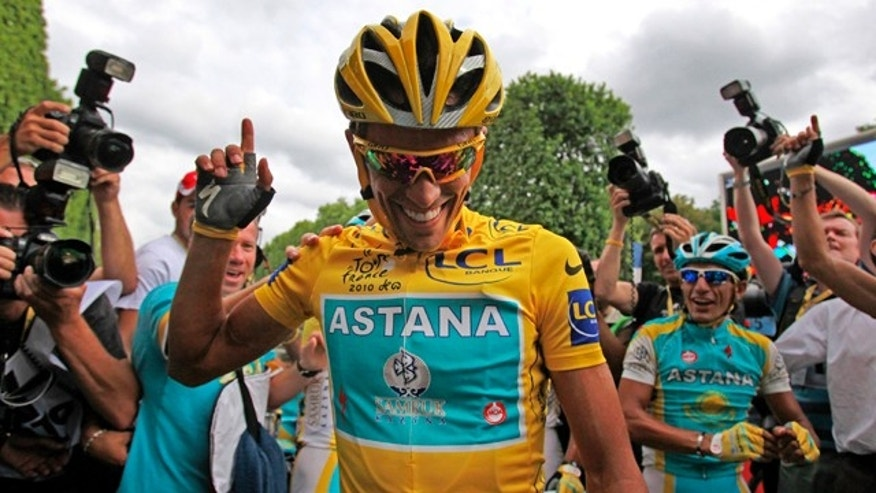 July 25, 2010: Three-time Tour de France winner Alberto Contador of Spain is flanked by teammates and photographers after the 20th and last stage of the tour.