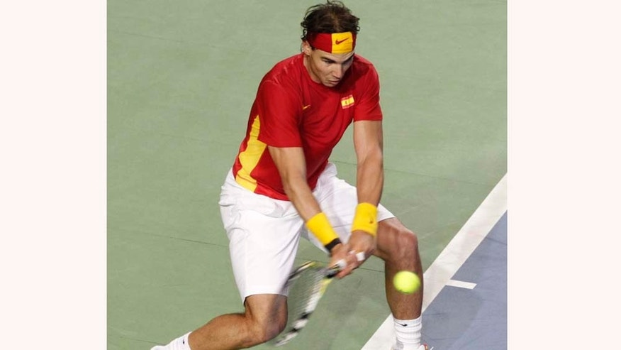 Spain's Rafael Nadal returns the ball towards Belgium's Olivier Rochus, on the final day of the Davis Cup World Group, first round in Charleroi, Belgium, Sunday, March 6, 2011. Spain qualified already on Saturday for the next round, after winning the first three matches.  (AP Photo/Yves Logghe)