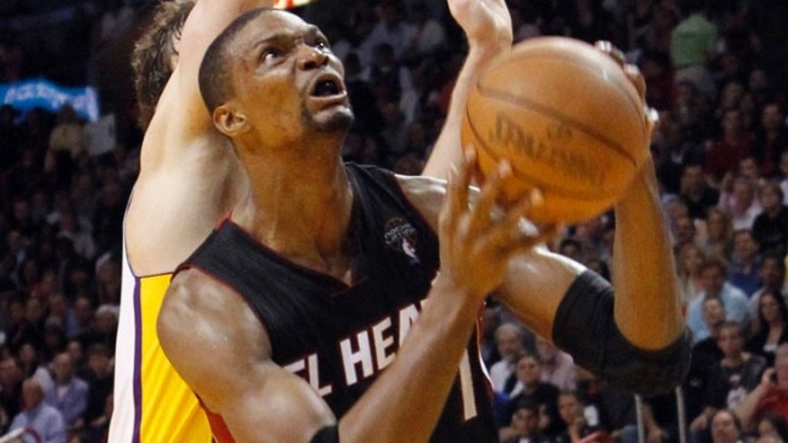 March 10: Miami Heat's Chris Bosh prepares to go to the basket as Los Angeles Lakers' Pau Gasol defends in the fourth quarter of the NBA basketball game in Miami. The Heat won 94-88.