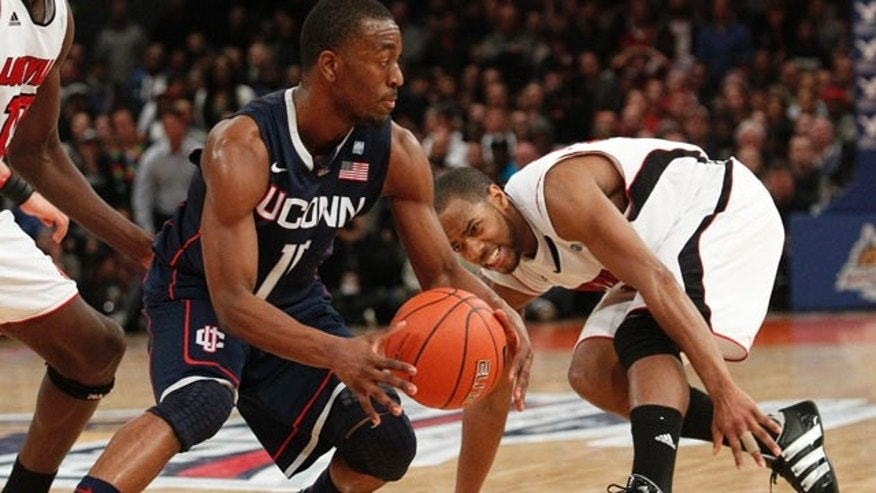 March 12: Connecticut's Kemba Walker (15) protects the ball from Louisville's Preston Knowles (2) during the second half of an NCAA college basketball game at the Big East Championship in New York. Both teams are now preparing for their NCAA Men's Division I Basketball Championship games as Walker is noted as a player to watch.