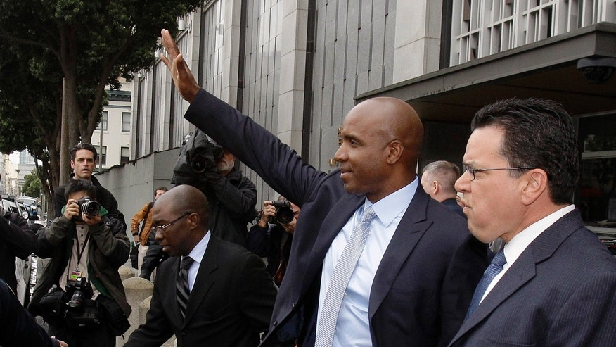 March 22: Barry Bonds waves at supporters as he leaves the federal courthouse after the second day of his perjury trial in San Francisco.