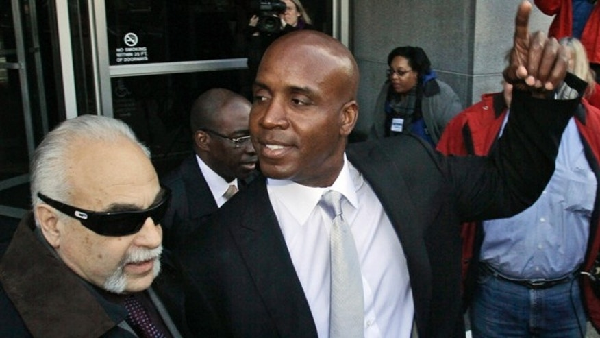 March 21: Barry Bonds, right, leaves the federal courthouse after the first day of his trial in San Francisco.