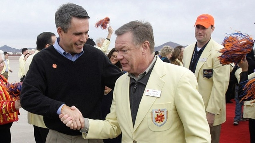 In this Dec. 28, 2009, file photo, Boise State coach Chris Petersen, left, is greeted by Fiesta Bowl president John Junker, right, after Petersen disembarked off a charter flight at Sky Harbor International Airport in Phoenix.