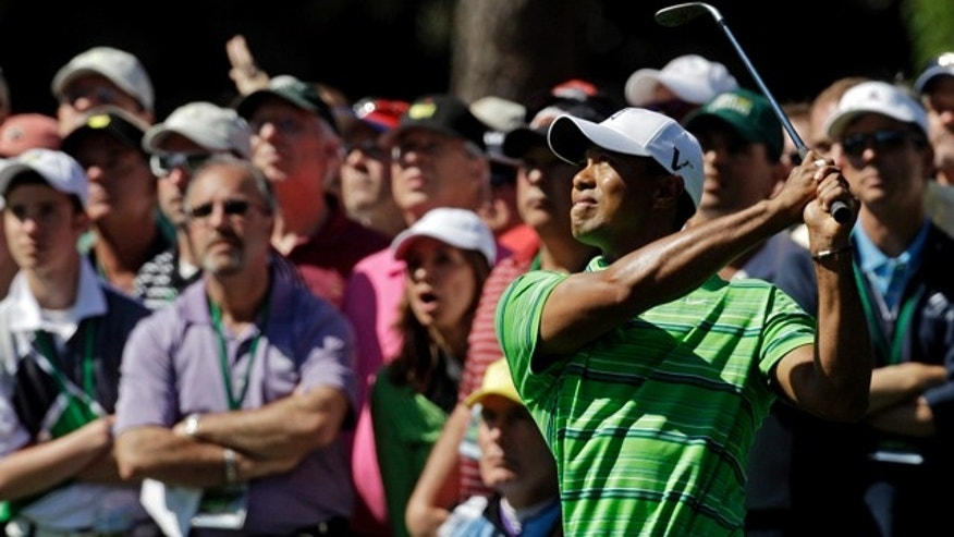 April 7: Tiger Woods watches his approach shot to the third green during the first round of the Masters golf tournament in Augusta, Ga.