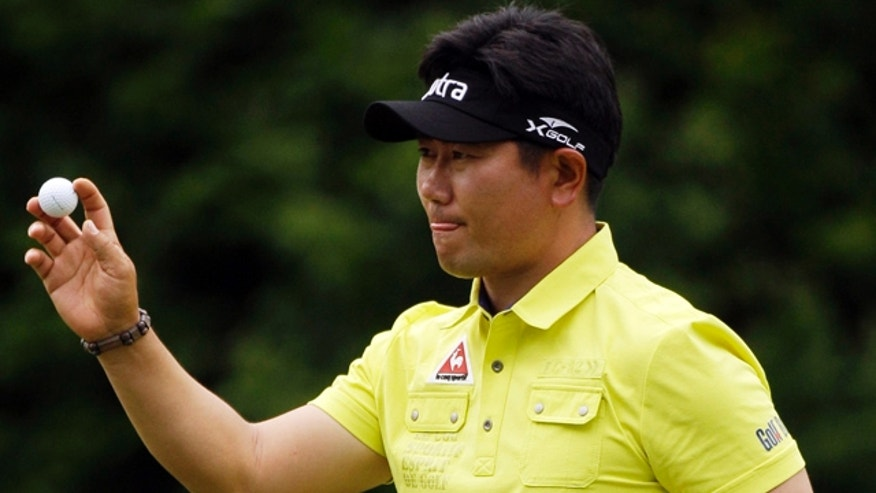 April 8: Y.E. Yang of Korea holds up his ball after a birdie on the fourth hole during the second round of the Masters golf tournament in Augusta, Ga.
