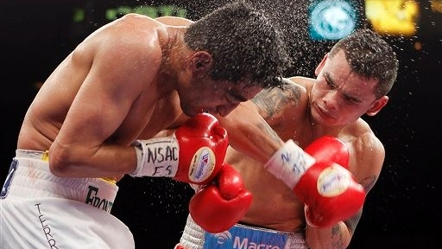 Marcos Maidana, of Argentina, right, punches Erik Morales, of Mexico during their WBA interim junior welterweight championship boxing match Saturday, April 9, 2011, in Las Vegas. Maidana won by majority decision. (AP Photo/Isaac Brekken)