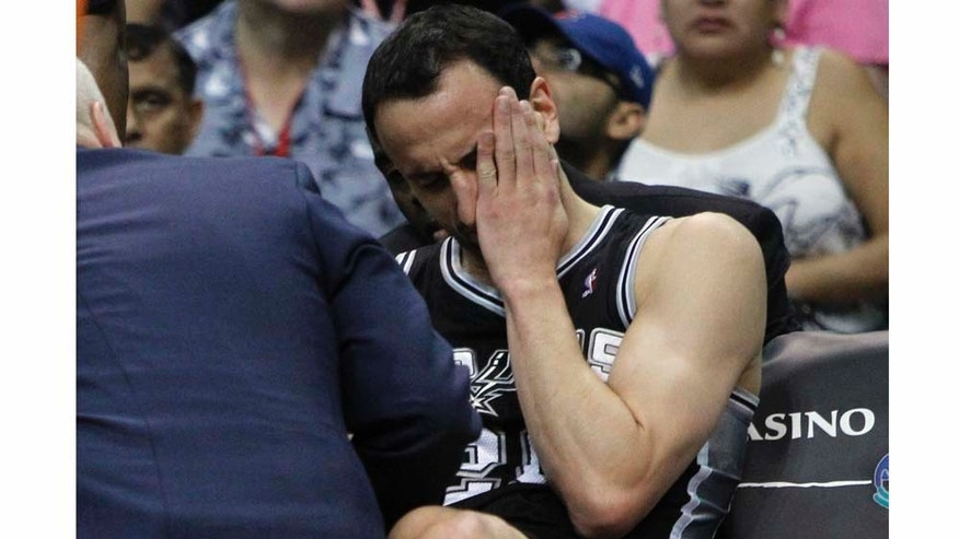 San Antonio Spurs' Manu Ginobili, of Argentina, is checked by the trainer after running into Phoenix Suns' Grant Hill during the first quarter of an NBA basketball game Wednesday, April 13, 2011, in Phoenix. Ginobili had to leave the game. (AP Photo/Matt York)
