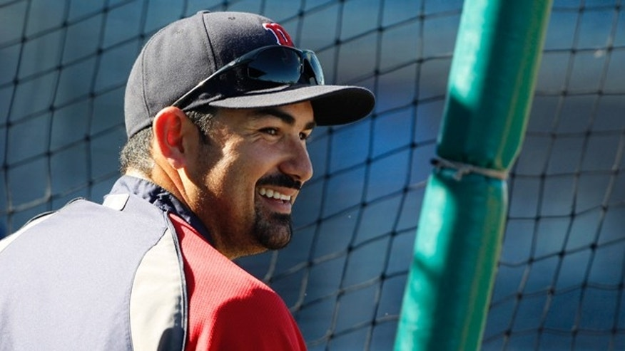 Boston Red Sox's Adrian Gonzalez smiles as he waits to hit during batting practice prior to facing the Minnesota Twins in a spring training baseball game in Fort Myers, Fla., Saturday, March 26, 2011. (AP Photo/Charles Krupa)