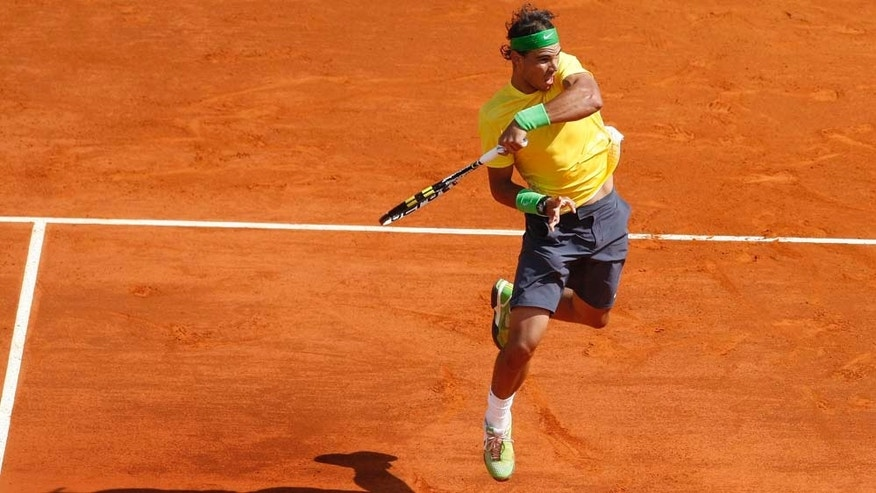 Rafael Nadal of Spain plays a return to  Ivan Ljubicic of Croatia during their quarterfinal match of the Monte Carlo Tennis Masters tournament in Monaco, Friday, April 15 , 2011. (AP Photo/Lionel Cironneau)