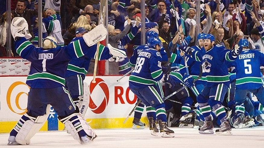 April 26: Vancouver Canucks' Roberto Luongo, left, skates to join Raffi Torres, right, and the rest of the team as they celebrate after defeating the Chicago Blackhawks in overtime during game 7 of an NHL Western Conference quarterfinal Stanley Cup playoff hockey series in Vancouver, British Columbia.