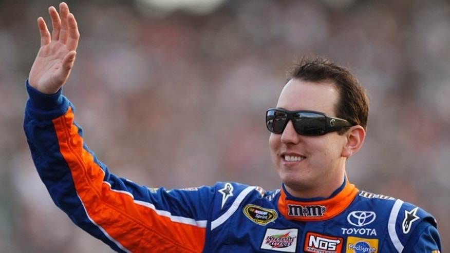 April 30: Kyle Busch waves to the crowd during dirver introductions prior to the start of the NASCAR Sprint Cup race at the Richmond International Raceway in Richmond, Va.
