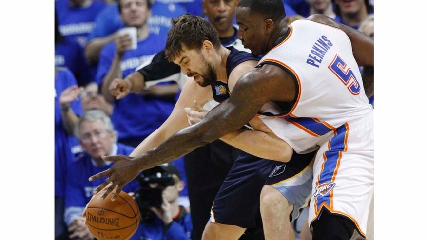 Oklahoma City Thunder center Kendrick Perkins, right, reaches in to knock the ball away from Memphis Grizzlies center Marc Gasol, left, of Spain, in the second quarter of Game 2 of a second-round NBA basketball playoff series in Oklahoma City, Tuesday, May 3, 2011. (AP Photo/Sue Ogrocki)