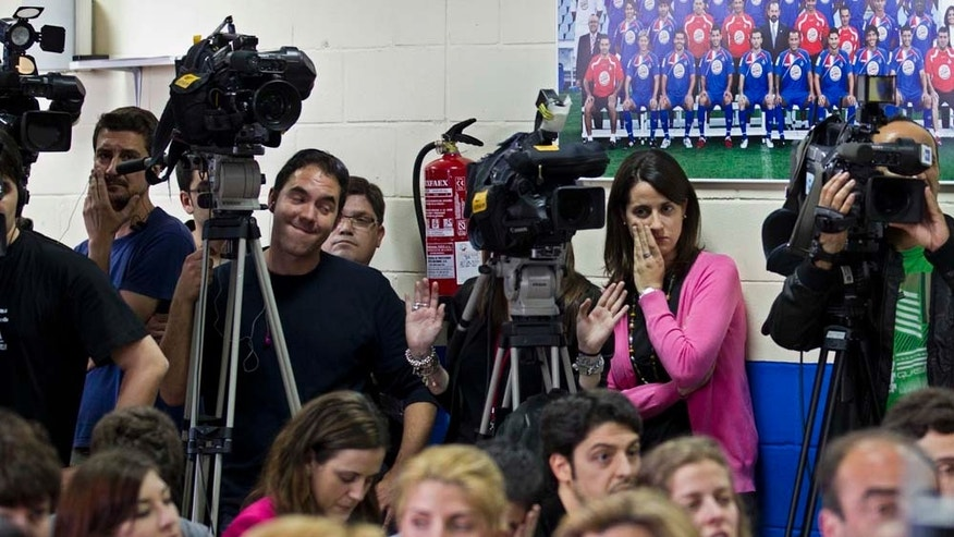 Journalists work next to an old Getafe team poster during a press conference by the president of Getafe soccer club Angel Torres, unseen, in Getafe, Spain Monday April 25, 2011. Torres announced that a Dubai business has bought the club. (AP Photo/Paul White)