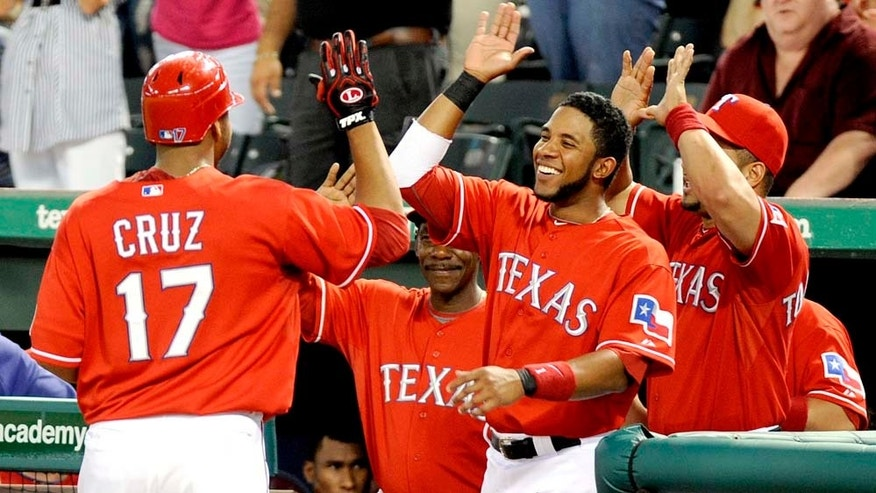 Texas Rangers' Nelson Cruz (17) is congratulated in the dugout after hitting a two-run home run in the sixth inning of a baseball game against the Chicago White Sox, Monday, May 23, 2011 in Arlington, Texas. The Texas Rangers won 4-0. (AP Photo/Matt Strasen)