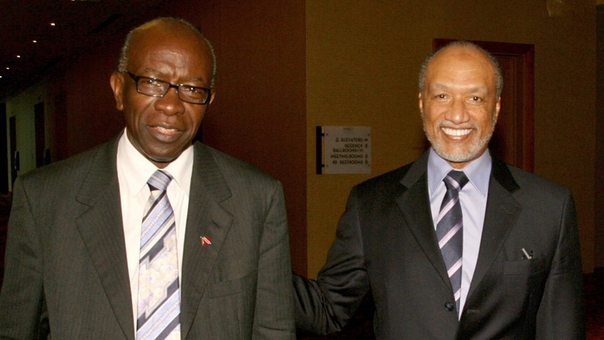 FILE - In this May 10, 2011 file picture Mohamed bin Hammam, right, of Qatar, chief of the Asian Football Confederation, is accompanied by FIFA Vice President Austin Jack Warner, of Trinidad & Tobago,  during a meeting in Port of Spain, Trinidad & Tobago. FIFA suspended Mohamed bin Hammam and Jack Warner on Sunday May 29, 2011 amid allegations the two executive committee members bribed voters in the presidential election campaign. The FIFA ethics committee, meanwhile, cleared FIFA president Sepp Blatter of turning a blind eye to the alleged bribes. The decision clears the way for Blatter to be re-elected unopposed to a fourth term on Wednesday. FIFA said bin Hammam, a Qatari who heads Asia's football confederation, and Warner, a FIFA vice president from Trinidad, will now face a full FIFA inquiry. If found guilty, they could be expelled from FIFA and banned from all football activity.   (AP Photo/Shirley Bahadur,File)