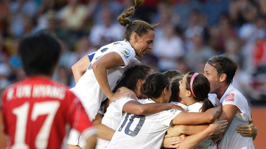 The US team celebrate scoring their side's 2nd goal during the group C match between the United States and North Korea at the Womens Soccer World Cup in Dresden, Germany, Tuesday, June 28, 2011. (AP Photo/Marcio Jose Sanchez)