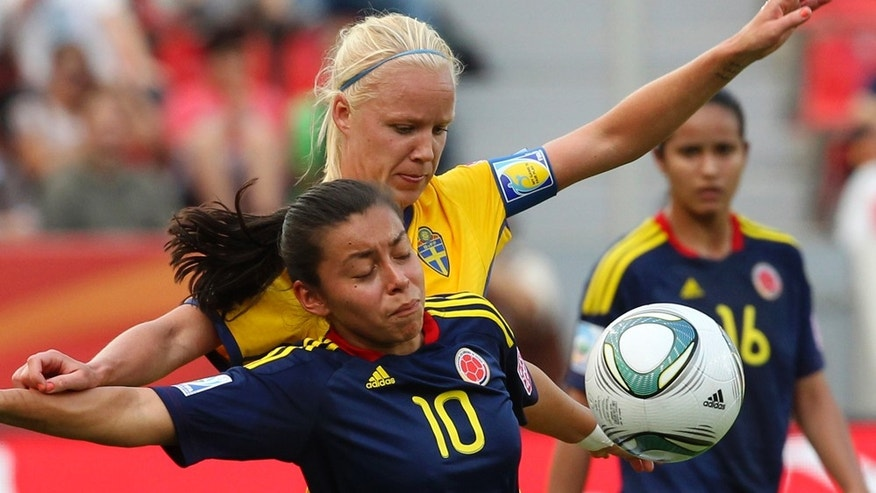 Sweden's Caroline Seger, back, and Colombia's Yoreli Rincon challenge for the ball during the group C match between Colombia and Sweden at the Womens Soccer World Cup in Leverkusen, Germany, Tuesday, June 28, 2011. (AP Photo/Michael Probst)